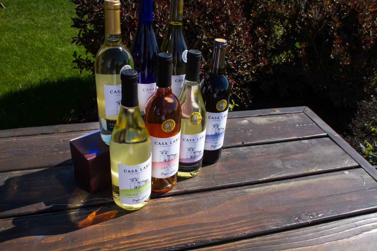 Wine line up on bench in vineyards at Casa Larga Vineyards